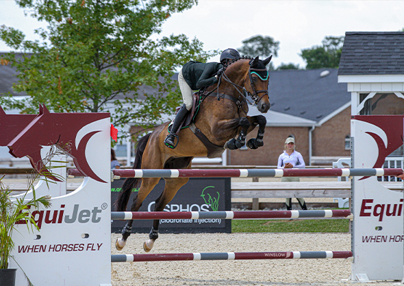 rider and horse clearing jump outdoor arena wilmington equestrian