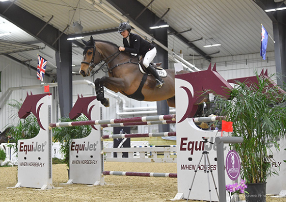 wilmington equestrian shows horse and rider clearing jump in competition